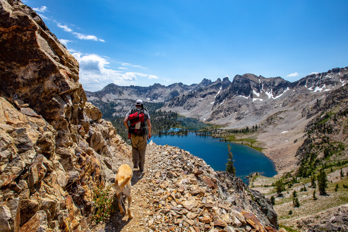 A man and a dog hiking in the Sawtooth Mountains, Idaho