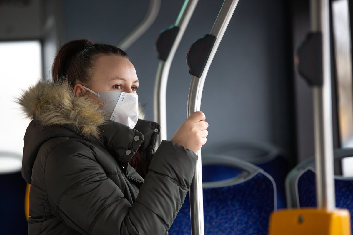 young woman with respiratory mask traveling by bus