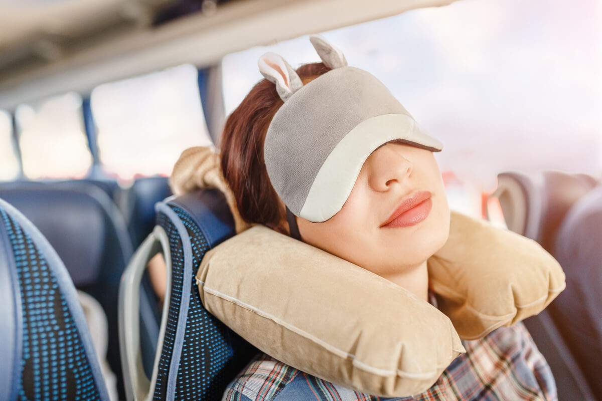 Woman in sleep mask and with pillow traveling in shuttle bus
