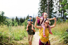 Parents and two kids enjoy hiking together in forest