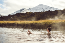 Natural Idaho hot springs, woman sitting in a natural hot spring, filed and snow covered mountains in the background