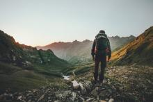 Man hiking at sunset in the Idaho mountains with a heavy backpack, outdoor adventure, travel safely