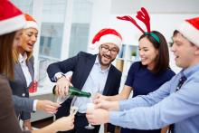 group of employees at an office holiday party drinking and smiling